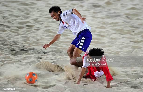 Takeshi Kawaharazuka of Japan is tackled by Rami Abdulla Al Nesaabi of UAE in the Men's Beach Soccer Quarterfinal match between Japan and United Arab...