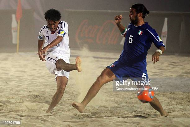 Takeshi Kawaharazuka of Japan shoots on goal as Simone Feudi of Italy defends during the preview match between Italy and Japan at the FIFA Beach...