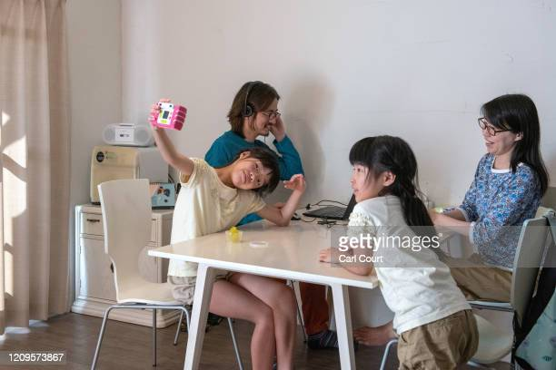 Takeshi Masuma a Getty Images Field Sales Executive and colleague of the photographer sits with his wife Yukiko and daughters Luna and Nene as he...