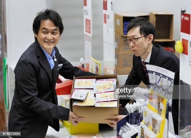 Takeshi Natsuno a member of the mascot screening committee for the 2020 Tokyo Olympics and Paralympics hands a box full of postcards to a post office...