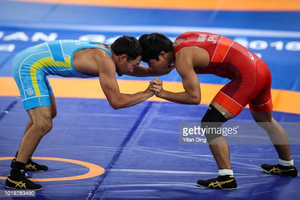 Takeshi Yamaguchi of Japan recieves medical treatment during his men's wrestling freestyle 97kg bronze medal match on day one of the Asian Games on...