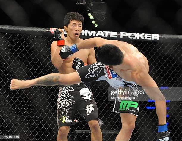 Takeya Mizugaki attempts to block a kick from Erik Perez during a bantamweight bout during UFC Fight Night 27 Condit v Kampmann 2 at Bankers Life...