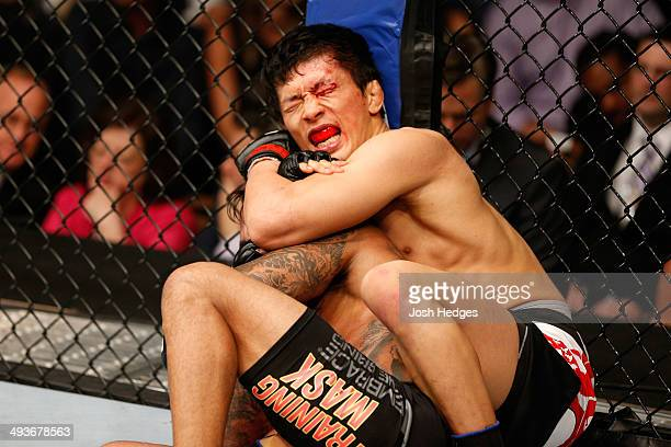 Takeya Mizugaki attempts to submit Francisco Rivera in their bantamweight bout during the UFC 173 event at the MGM Grand Garden Arena on May 24, 2014...
