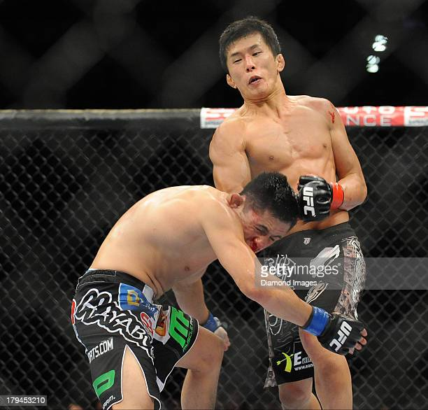 Takeya Mizugaki connects with a punch during a bantamweight bout during UFC Fight Night 27 Condit v Kampmann 2 at Bankers Life Field House in...