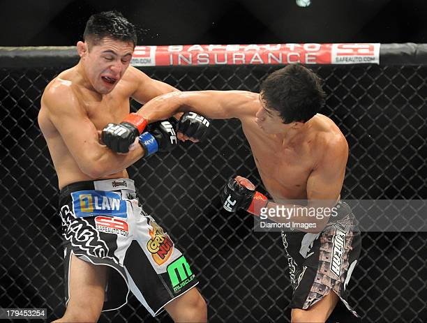 Takeya Mizugaki connects with a punch to the head of Erik Perez during a bantamweight bout during UFC Fight Night 27 Condit v Kampmann 2 at Bankers...