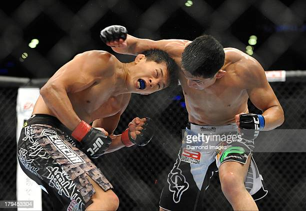 Takeya Mizugaki dodges a punch from Erik Perez during a bantamweight bout during UFC Fight Night 27 Condit v Kampmann 2 at Bankers Life Field House...