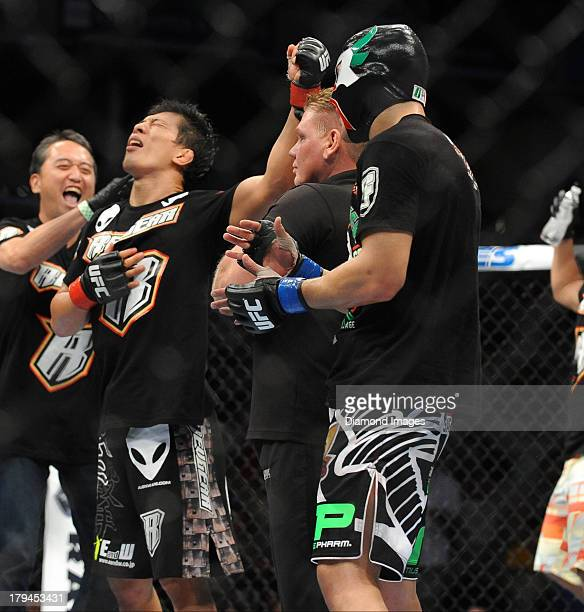 Takeya Mizugaki his his arm raised in victory by the referee after a bantamweight bout during UFC Fight Night 27 Condit v Kampmann 2 at Bankers Life...