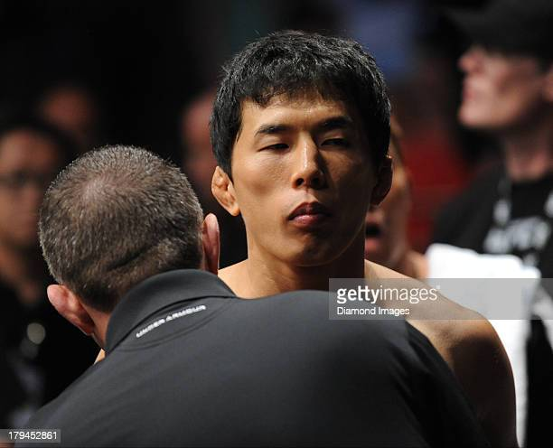 Takeya Mizugaki is prepped before entering the octagon before a bantamweight bout during UFC Fight Night 27 Condit v Kampmann 2 at Bankers Life Field...