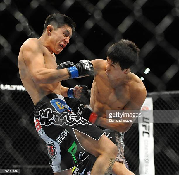 Takeya Mizugaki lands a punch to the face of Erik Perez during a bantamweight bout during UFC Fight Night 27 Condit v Kampmann 2 at Bankers Life...