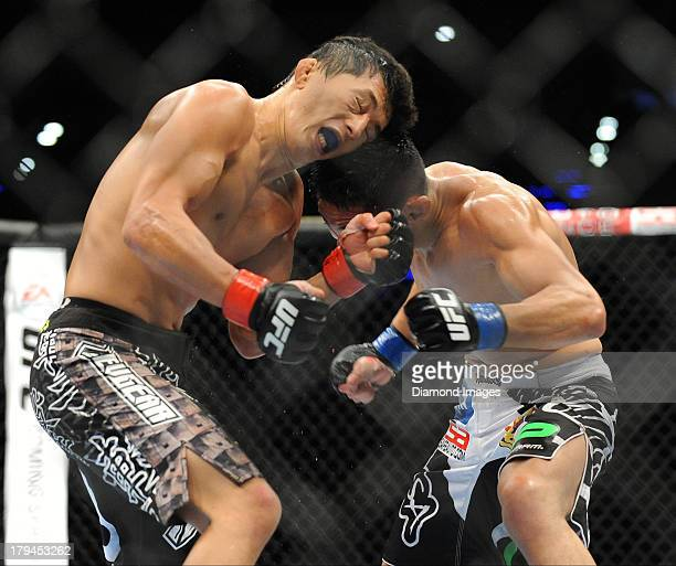 Takeya Mizugaki looks for an opening to throw a punch at Erik Perez during a bantamweight bout during UFC Fight Night 27 Condit v Kampmann 2 at...