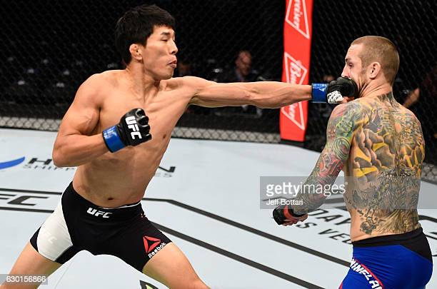 Takeya Mizugaki of Japan punches Eddie Wineland in their bantamweight bout during the UFC Fight Night event inside the Golden 1 Center Arena on...