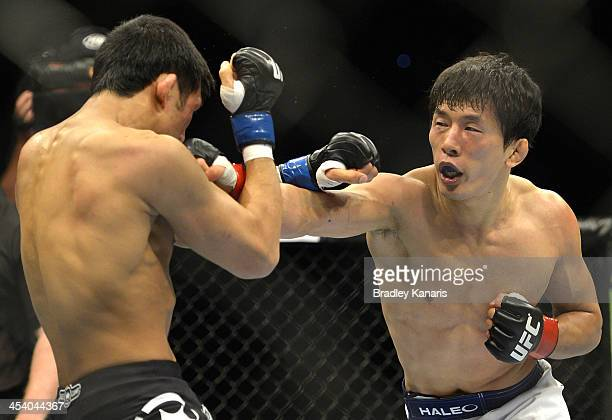 Takeya Mizugaki of Japan punches Nam Phan of the USA during their bantamweight fight during the UFC Fight Night event at the Brisbane Entertainment...
