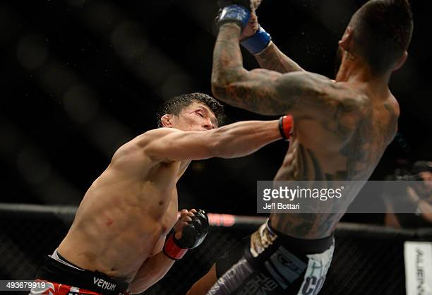 Takeya Mizugaki punches Francisco Rivera in their bantamweight bout during the UFC 173 event at the MGM Grand Garden Arena on May 24, 2014 in Las...