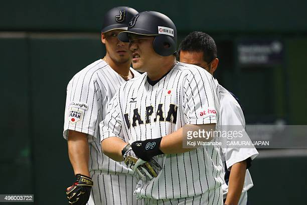 Takeya Nakamura of Japan reacts in pain after getting hit with a pitch in the bottom half of the second inning during the sendoff friendly match for...