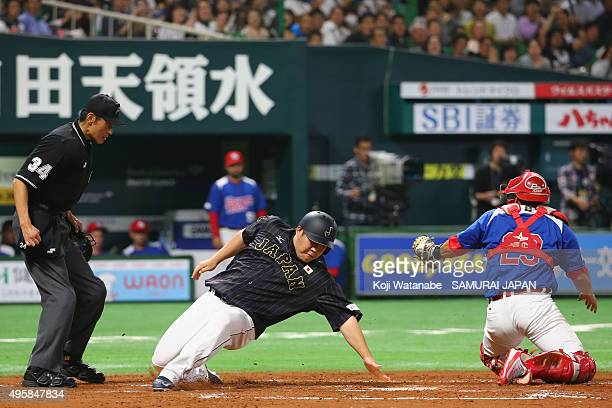 Takeya Nakamura of Japan touches the home plate in the top half of the fourth inning during the sendoff friendly match for WBSC Premier 12 between...