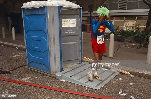 Taking a break from the London Marathon a young runner dressed as Superman emerges from a Portaloo after a quick toilet stop at the London Fire...