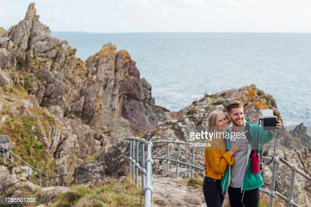 taking a couple's selfie on an instant camera - england stock pictures, royalty-free photos & images