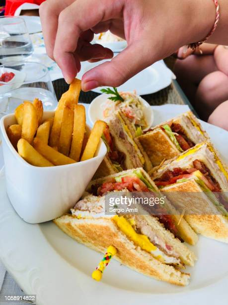 Taking a French fry from a plate of club sandwiches and French fries