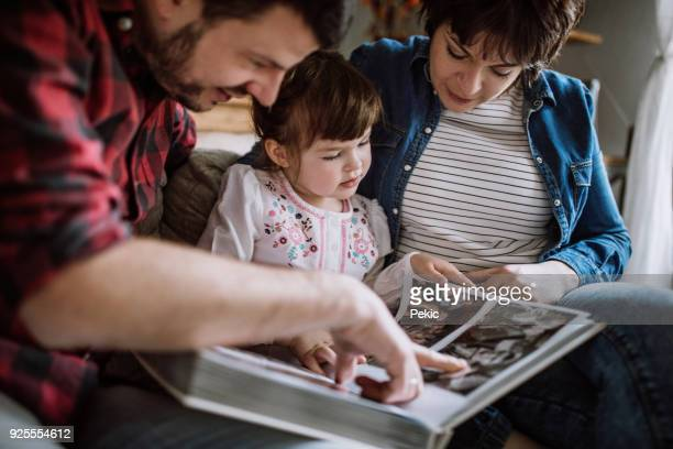 taking a look at some old family photos - photo album stock photos and pictures