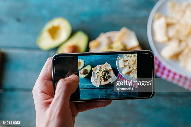Taking a picture of nachos and guacamole with smartphone, close-up