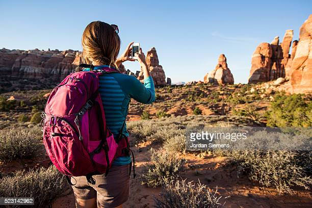 taking a picture with smart phone while backpacking. - canyonlands national park stock pictures, royalty-free photos & images