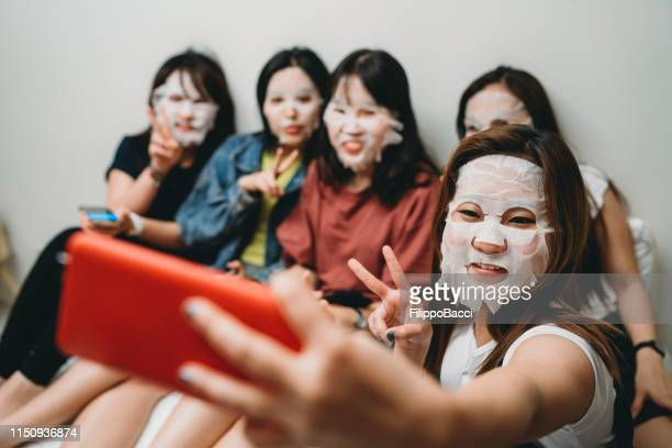 taking a selfie during a facial masks night with friends at home - cloth face mask stock pictures, royalty-free photos & images