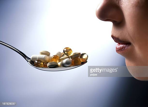 taking a spoon full of pills