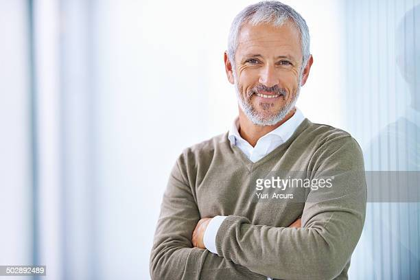 taking care of business with a smile - one mature man only stock pictures, royalty-free photos & images