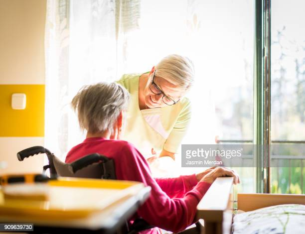 Taking care of elderly sick woman in wheelchair