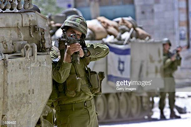 Taking cover from behind a tank in Manger square an Israeli soldier keeps his rifle trained on the Church of the Nativity in the West Bank town of...