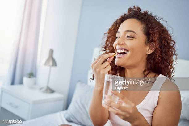 taking her daily medication with a smile - moving activity stock pictures, royalty-free photos & images