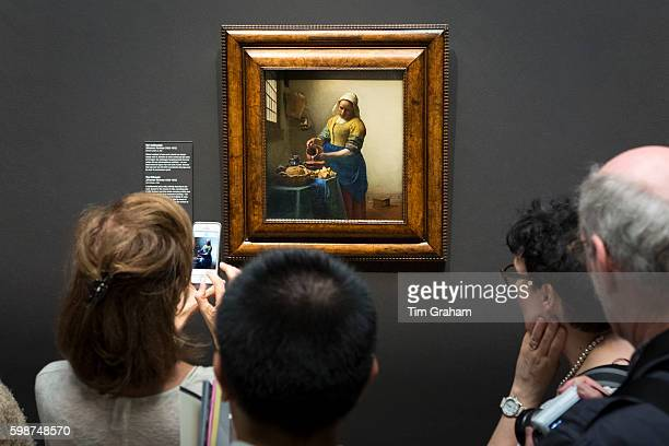 Taking iPhone smartphone photograph of painting by Johannes Vermeer 'The Milkmaid' at Rijksmuseum Amsterdam Holland