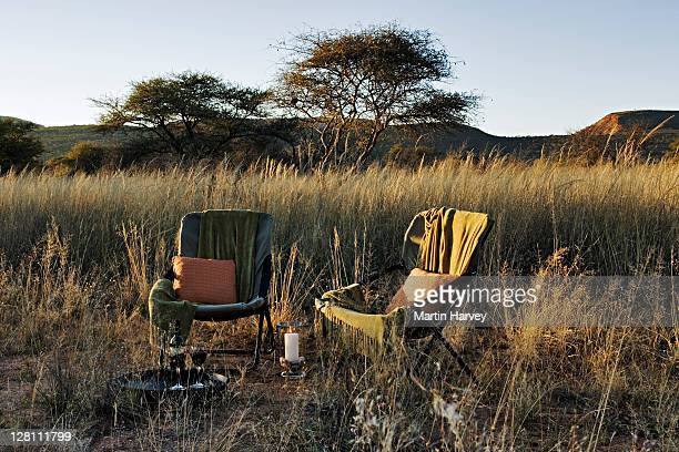 taking luxurious sunsets and relaxation another step with a glass of wine on a canvas chair amidst the beautiful grassy landscape of okonjima private game reserve, namibia. scenic view of omboroko mountains in background. (pr: property released) - nature reserve stock-fotos und bilder