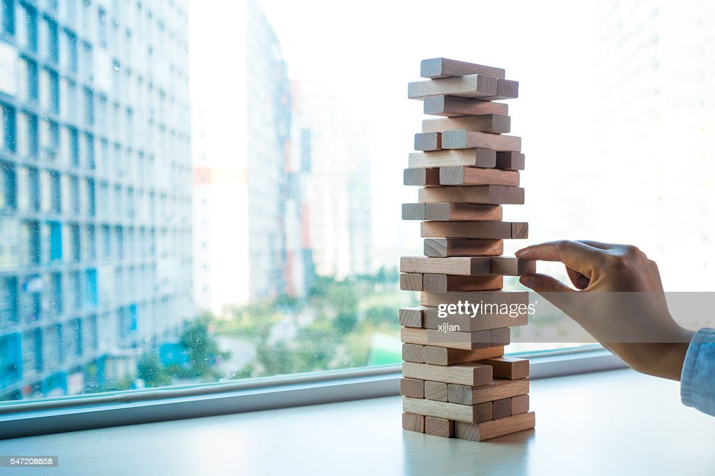 Taking one block from wooden blocks tower : Stock Photo