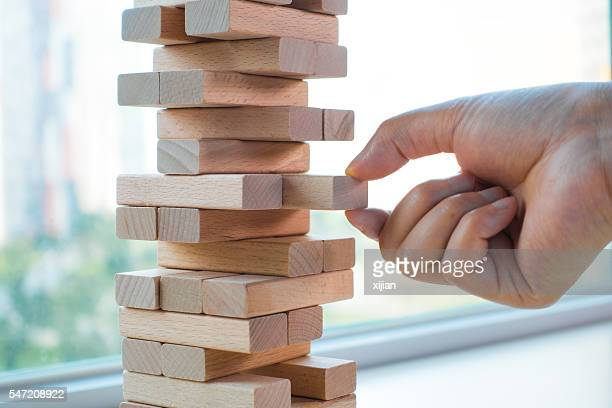 Taking one block from wooden blocks tower