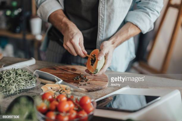 木製のスプーンで種子を取り出す - 果肉 ストックフォトと画像