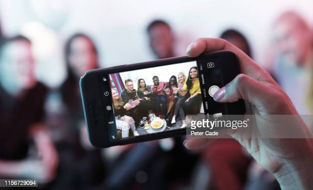 taking photo of young people at house party - iphone stock pictures, royalty-free photos & images
