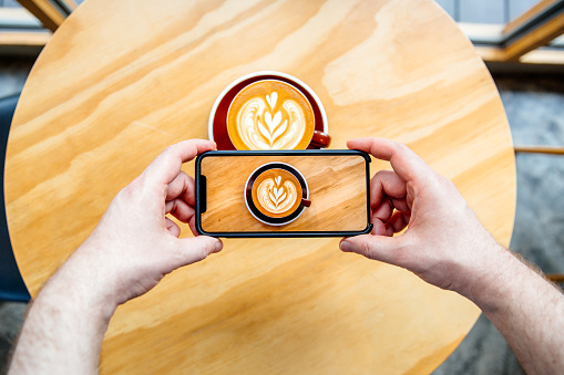 Taking picture of a coffee cup with latte art with smartphone - gettyimageskorea