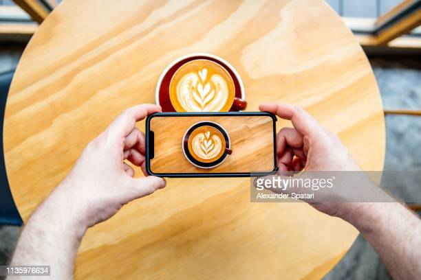 taking picture of a coffee cup with latte art with smartphone - influencer photos stock photos and pictures