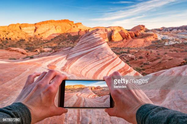 taking picture of fire wave in valley of fire state park nevada - valley of fire state park stock photos and pictures