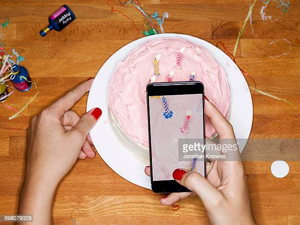 taking picture with phone of cake with candles - photographing stock pictures, royalty-free photos & images