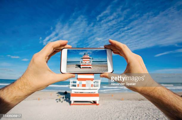 taking pictures with smartphone at miami beach, personal perspective view - fotohandy stock-fotos und bilder