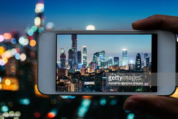 Taking pictures with smartphone from personal point of view of Beijing Skyline
