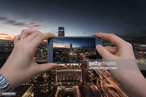 Taking pictures with smartphone of Aerial View of Beijing Skyline at Dusk