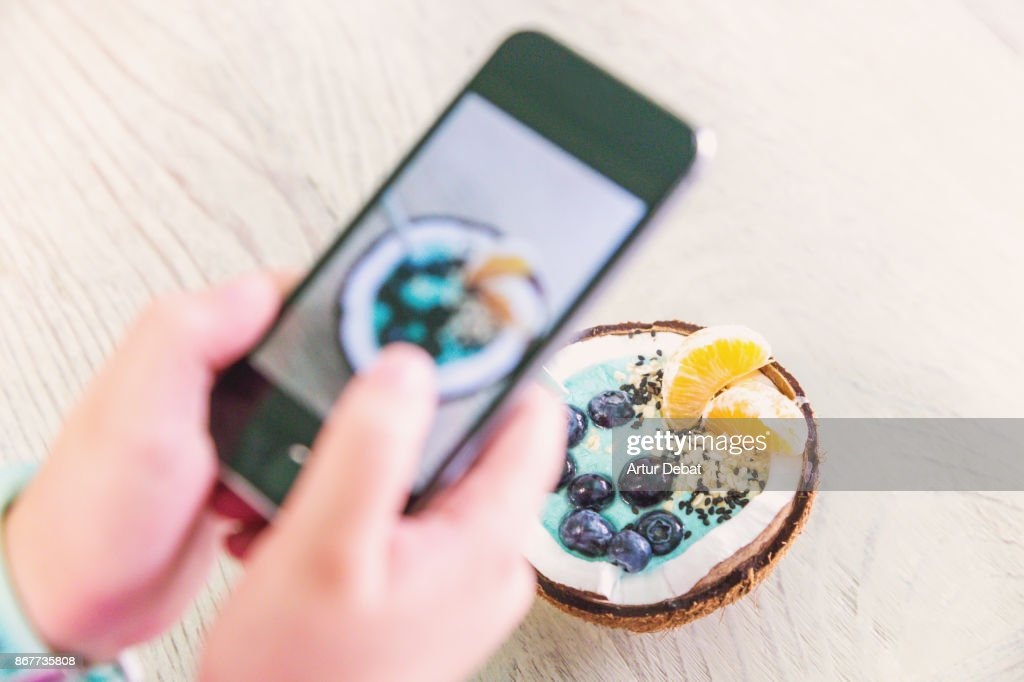 Taking pictures with smartphone of healthy breakfast food in the morning on wood table inside coconut with yogurt, fruit and cereals taken directly from above. : Stock Photo