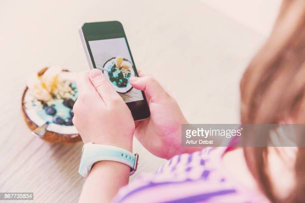 Taking pictures with smartphone of healthy breakfast food in the morning on wood table inside coconut with yogurt, fruit and cereals taken directly from above.