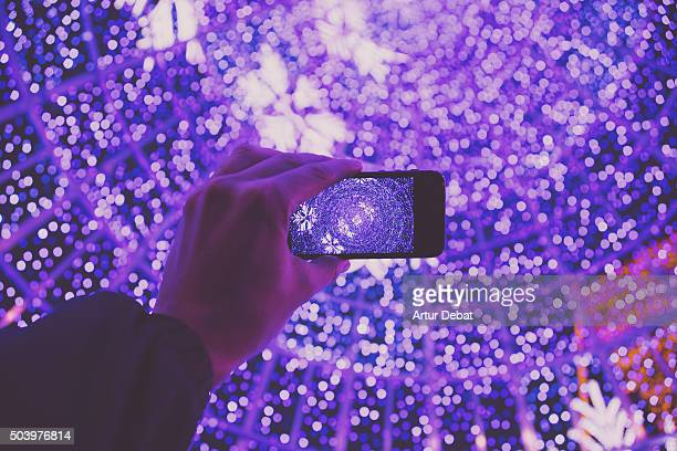 Taking pictures with smartphone of the bokeh Christmas tree at night from personal point of view.