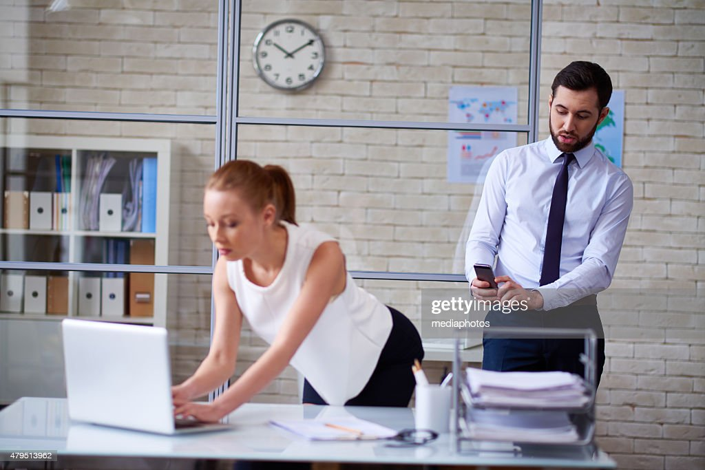 Taking racy photos at office : Stock Photo