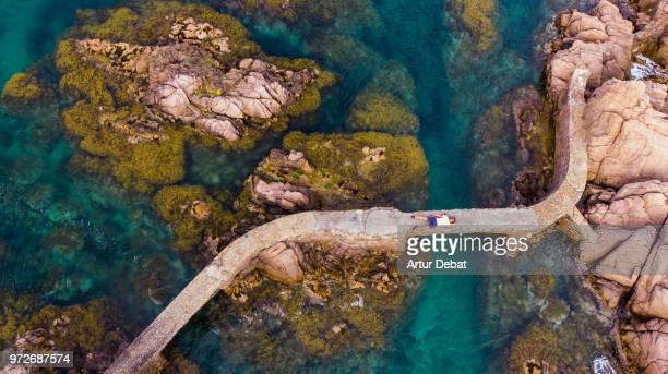 taking selfie with drone laying in the rocks with the sea in the costa brava shoreline. - katalonien stock-fotos und bilder