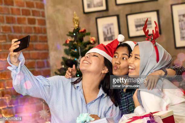 Taking selfie with smartphone during Christmas celebration with friends